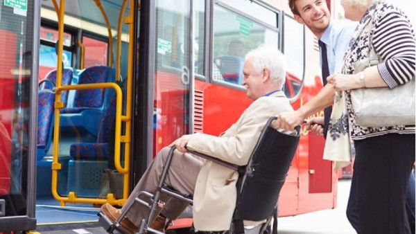 Elderly woman in wheelchair getting assistance boarding a bus