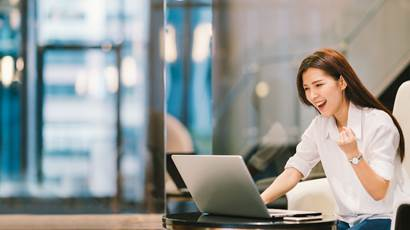 Beautiful Asian girl celebrate with laptop, success or happy pose, education or technology or startup business concept, modern office or living room with copy space