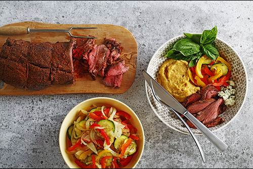 Balsamic beef tenderloin on a cutting board with vegetables and polenta served in dishes
