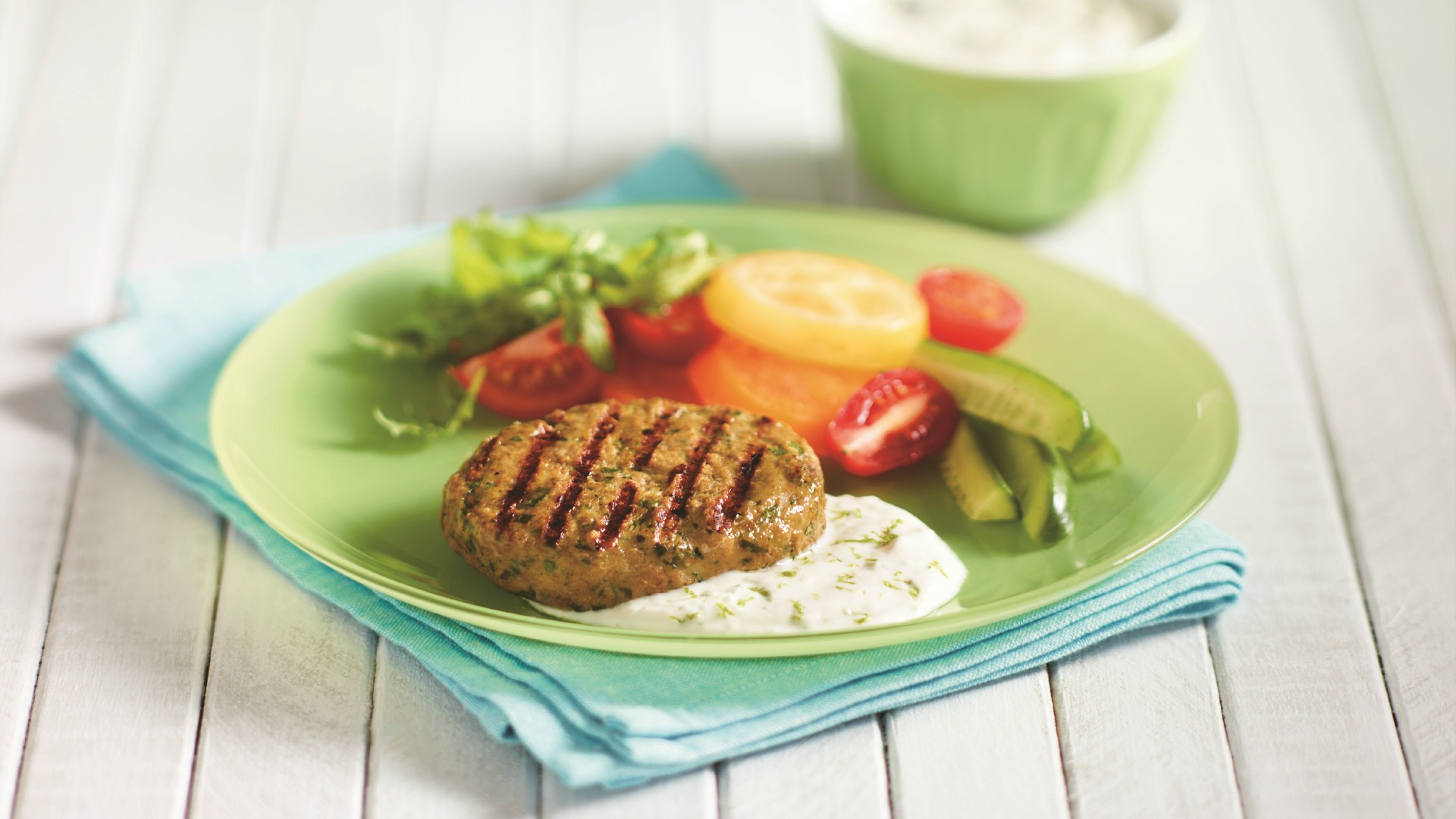 Barbequed curried chicken burgers with yogurt sauce and sliced vegetables