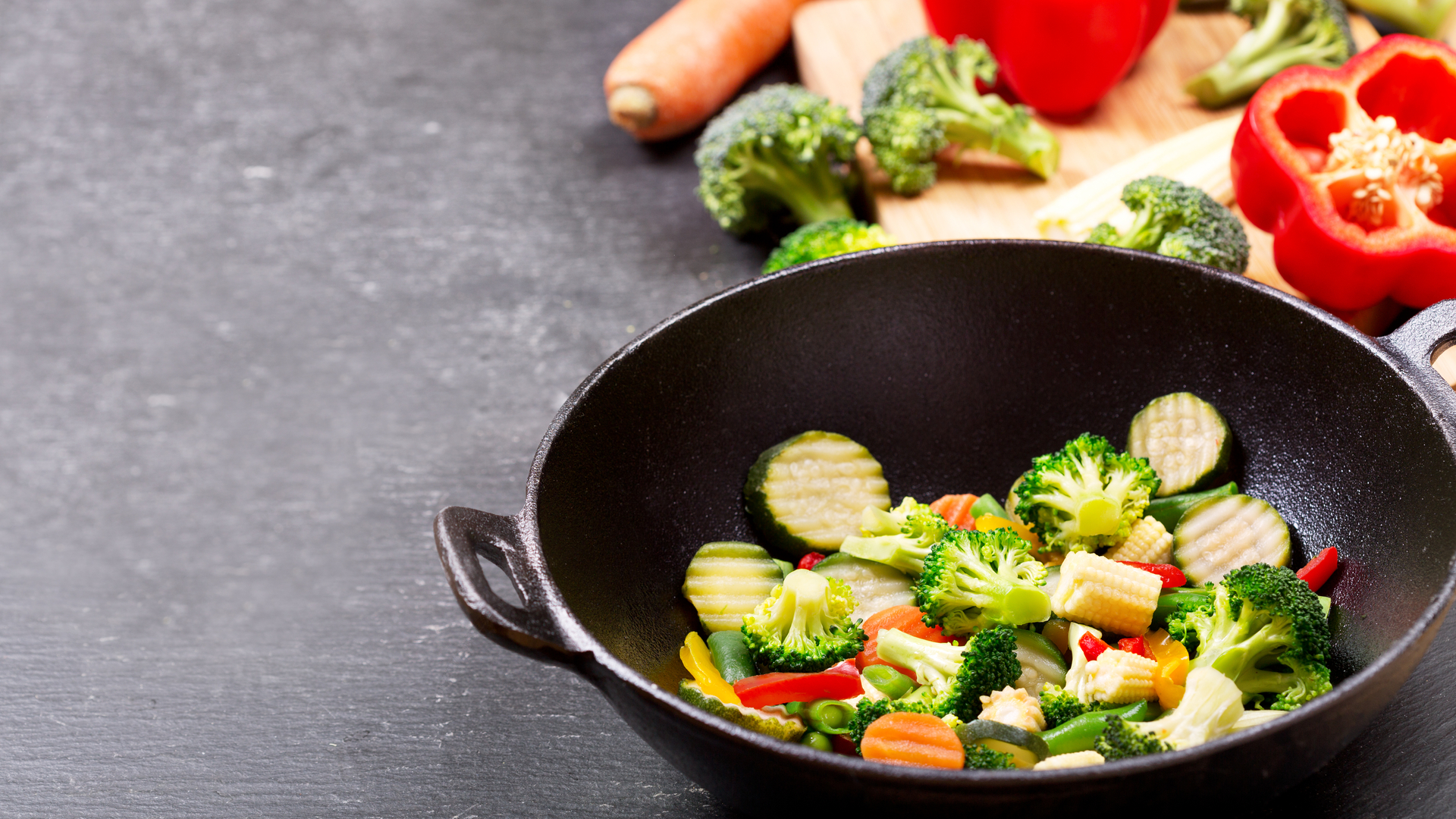Chicken and vegetable stir fry chopped in a black wok