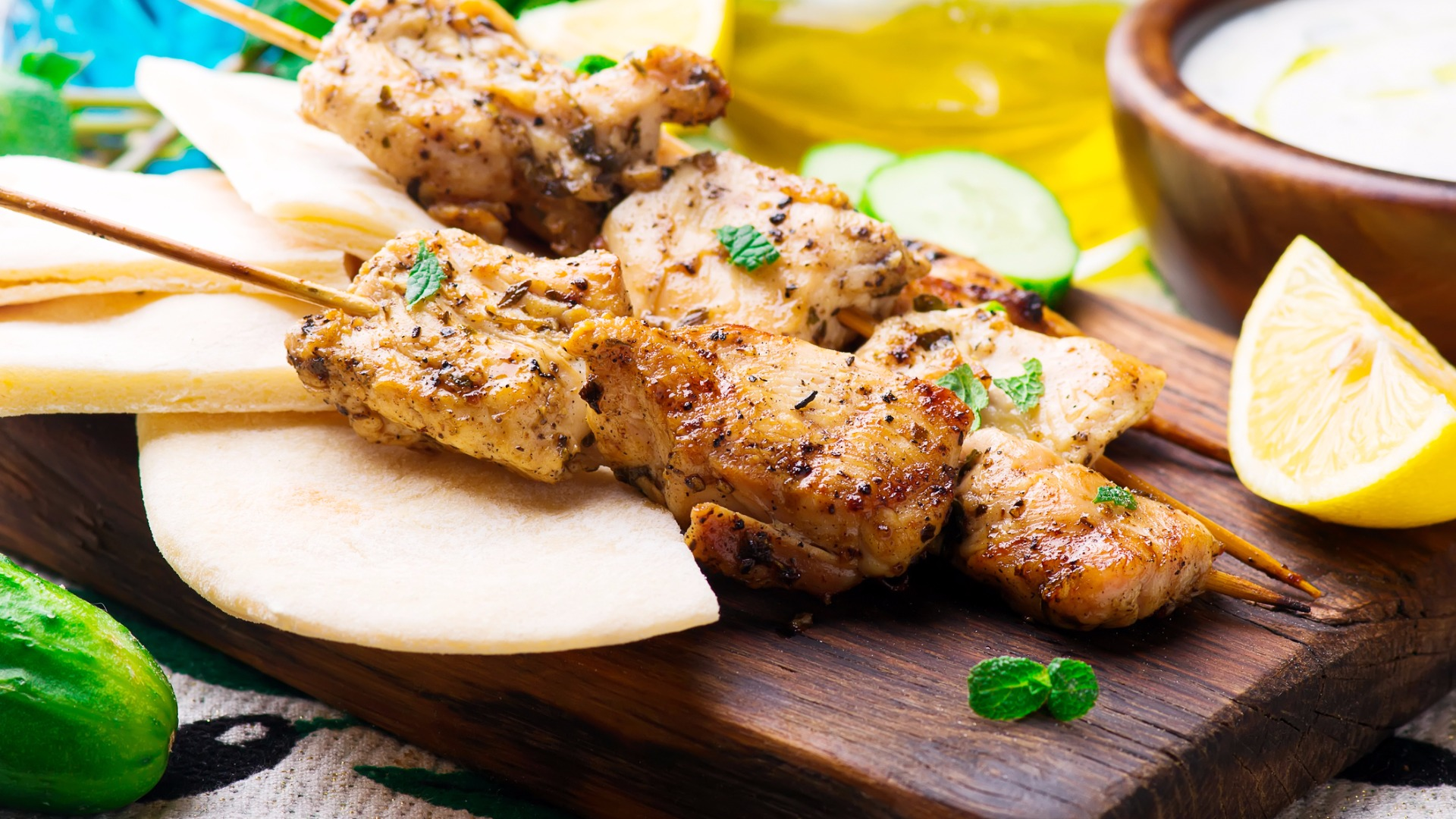 Chicken souvlaki on a cutting board with lemon and dip