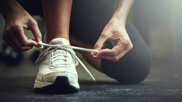 Closeup of woman tying her white running shoes