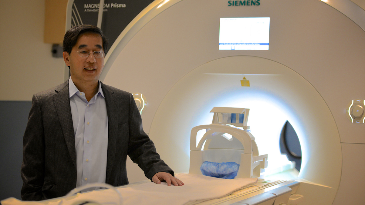 Dr. Jack Tu stands next to a CT Scanner wearing a grey blazer and a blue button down shirt.