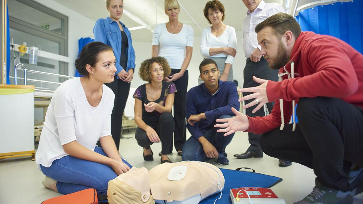 a mixed age group listen to their tutor as he shows the procedure involved to resuscitate using a defibrillator