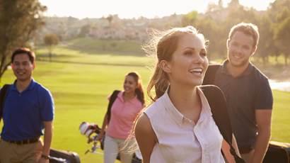 Golfers walking up a hill