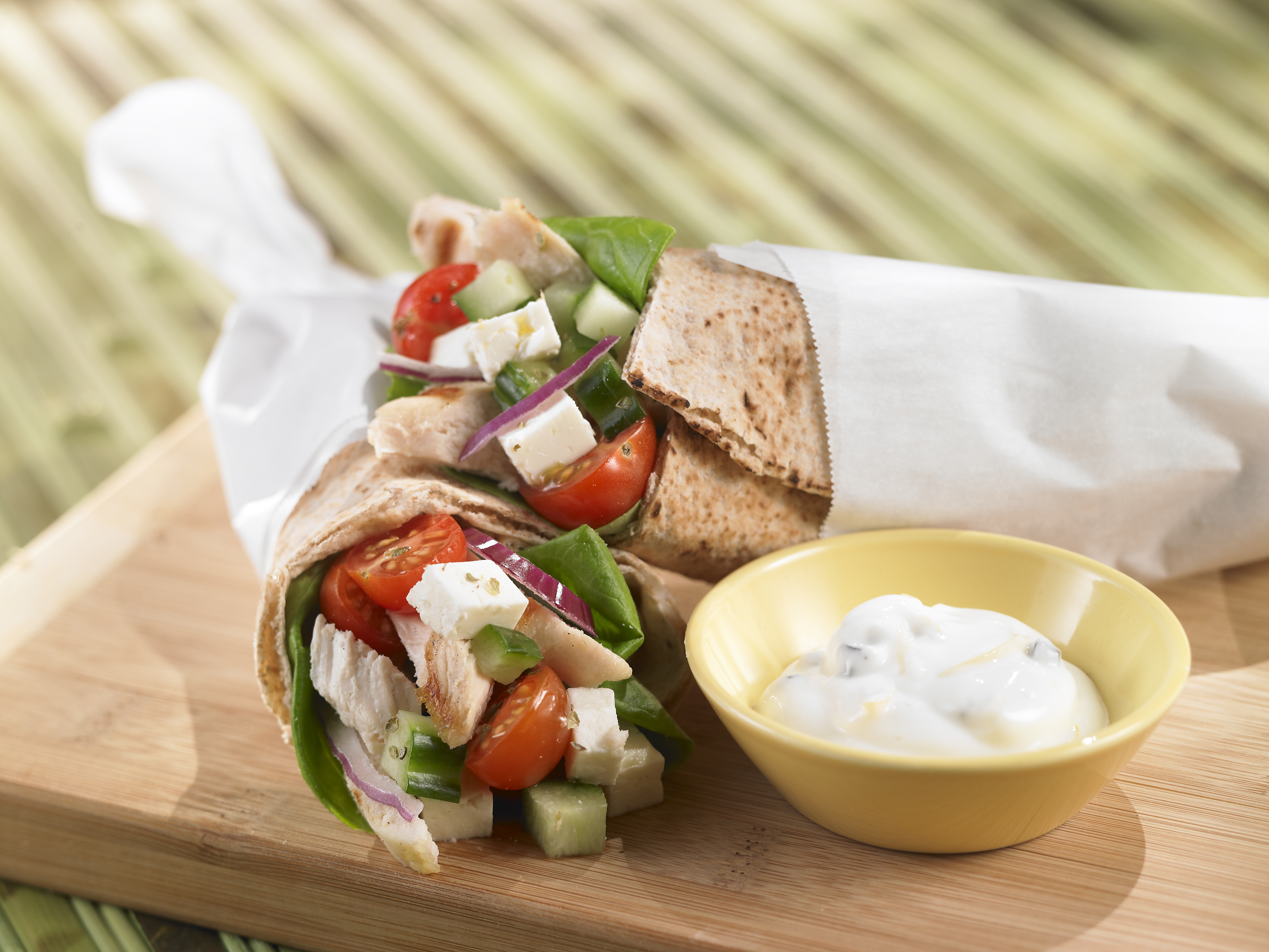 Greek, veggie and chicken wrap on a cutting board