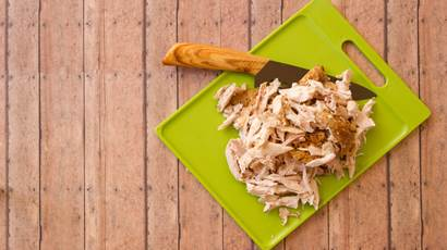Shredded rotisserie chicken on a green plastic cutting board and carving knife