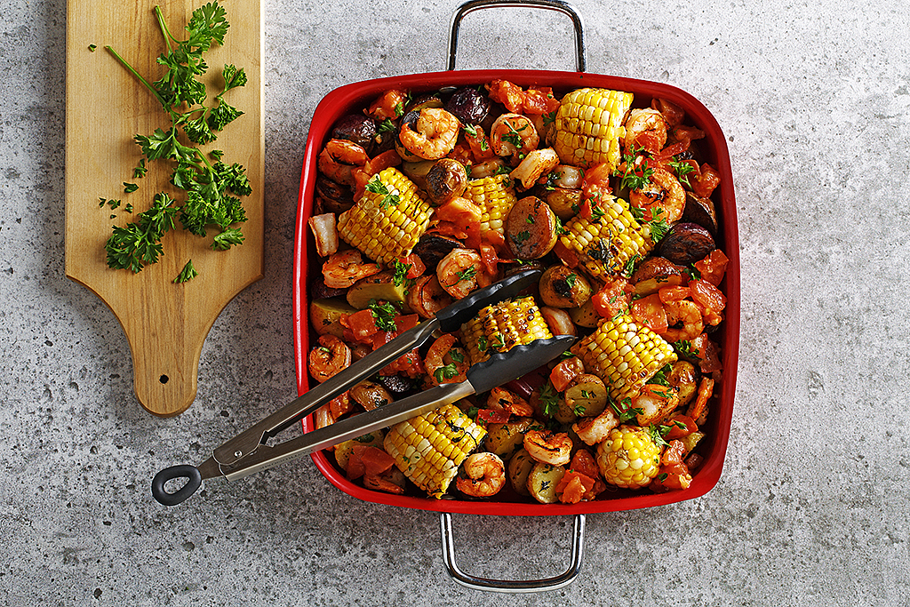 Grilled shrimp and corn casserole in a square red serving dish with tongs