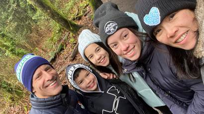 Stroke survivor Adrienne Martin with her husband and three children in a forest.