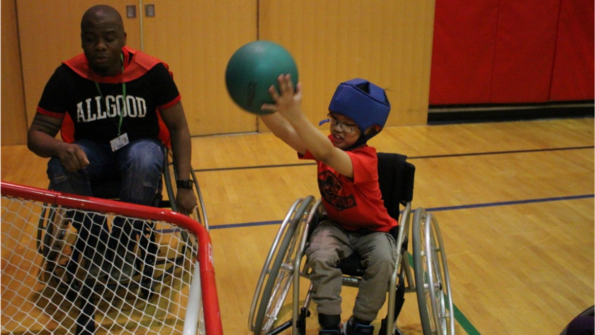 A student in a wheelchair lifts a ball over his head aiming for a net in a school gymnasium.