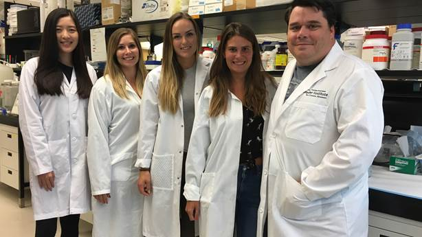<p>Dr. Craig Jenne (far right) with his research team at the University of Calgary.</p>