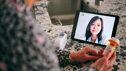 A senior aged woman in her home talking to a doctor online over video conference for a virtual appointment.