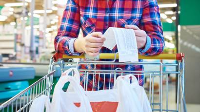 A woman in a plaid shirt leans on a grocery cart while holding a receipt.