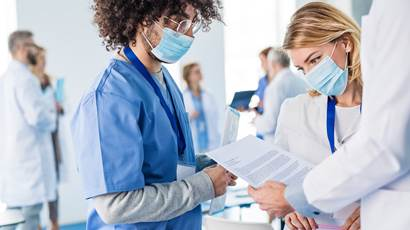 A group of medical professionals in masks look at a paper.