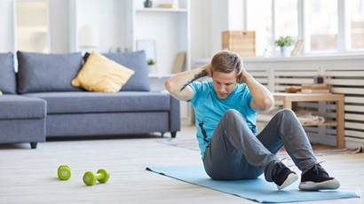 Young man in activewear sitting on the floor with his hands behind head and doing sit-ups