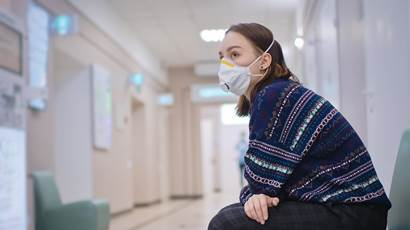 A woman wearing a mask sits in a hospital corridor
