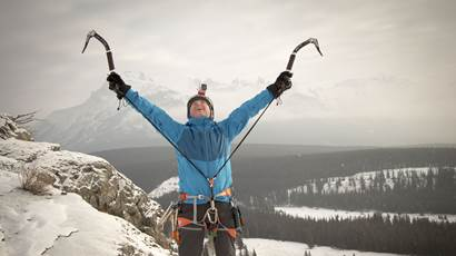 Leo Namen raises his arms to celebrate reaching a mountain summit.