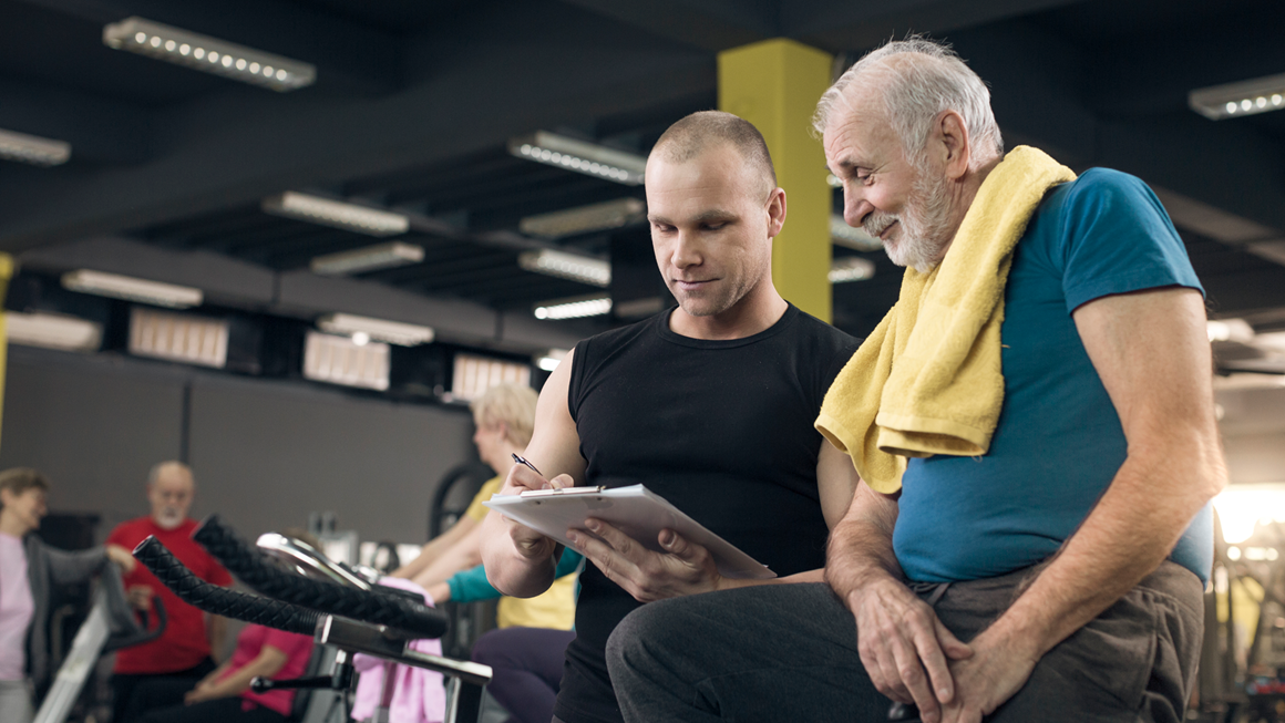 Older man reviewing his progress with trainer on a cycling bike
