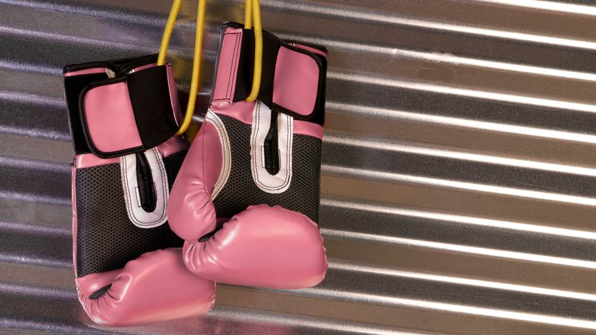 Pink boxing gloves hanging on hook