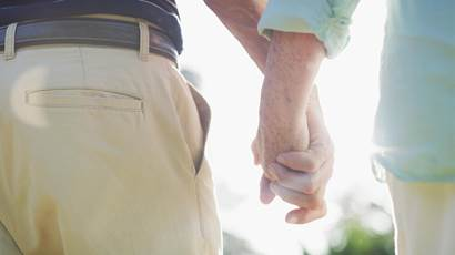 Rearview shot of an unrecognizable senior couple walking together while holding hands in a park during the day