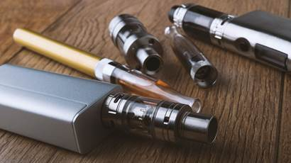Various vaping devices on a wooden background