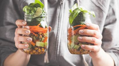 Woman holding up salad jars