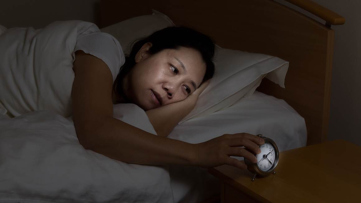 Woman with insomnia touching alarm clock