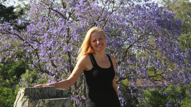Annie Richard smiles in front of a tree with purple flowers