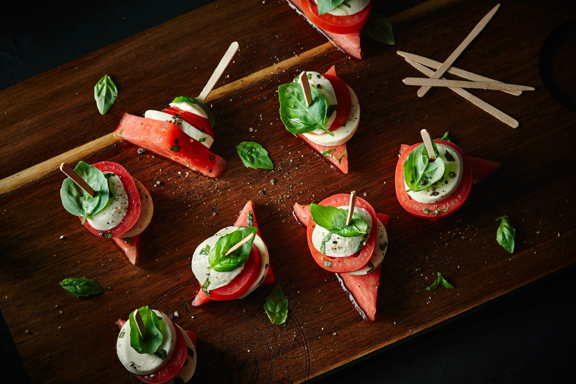 Stacks of sliced tomato, watermelon, bocconcini cheese and basil on wooden board