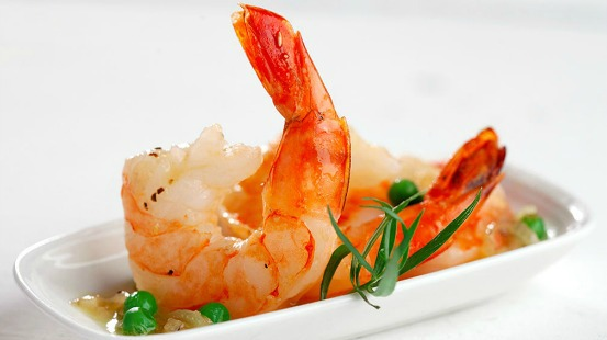 Cooked shrimp and peas served on a white plate
