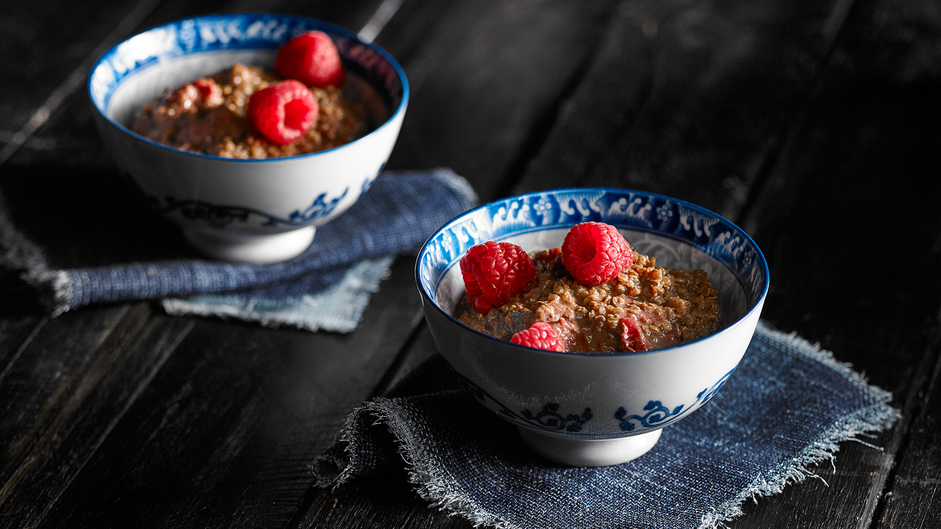 Two bowls filled with chocolate quinoa pudding topped with fresh raspberries