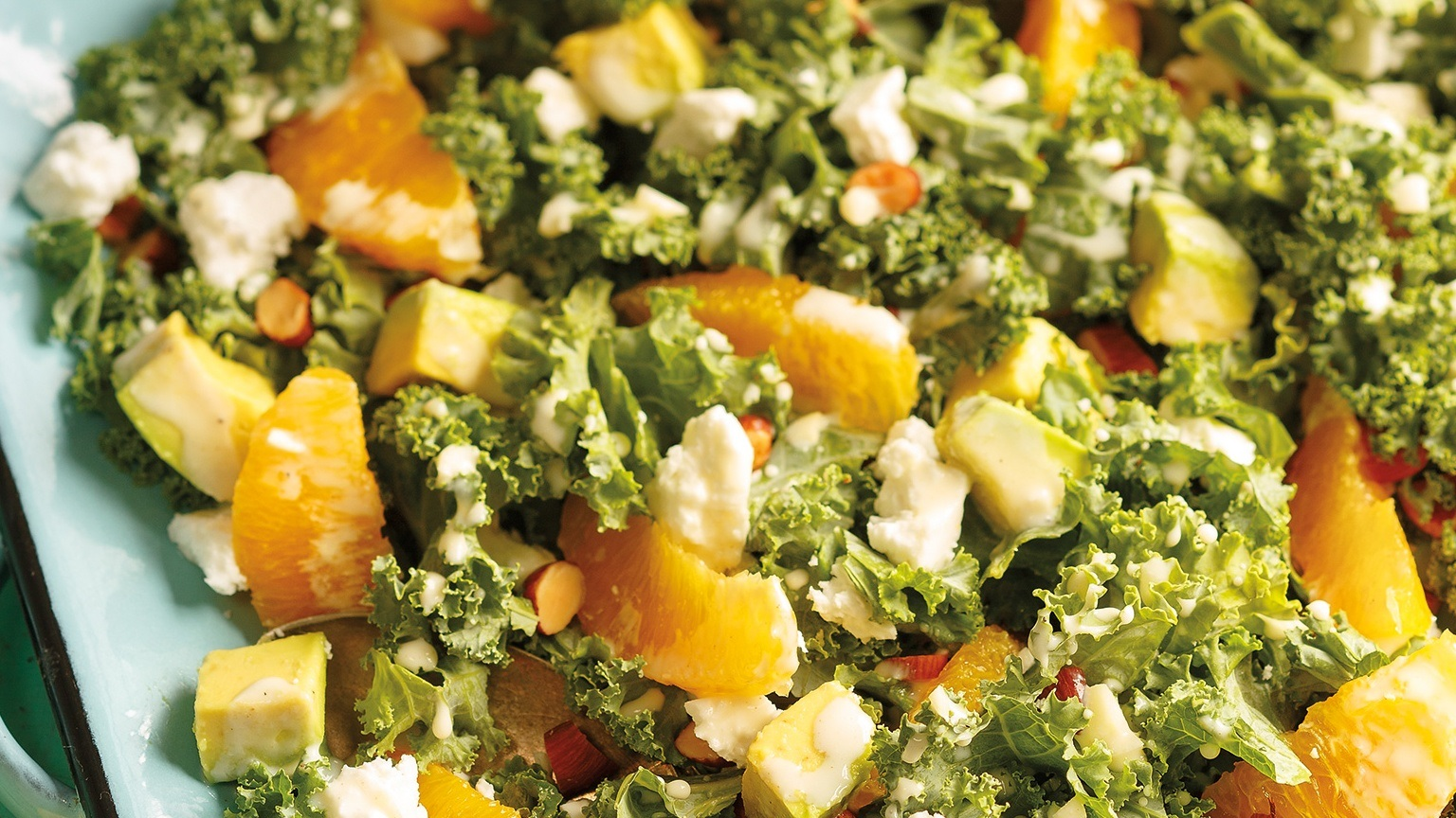 Closeup of chopped kale, avocado orange segments and crumbled feta
