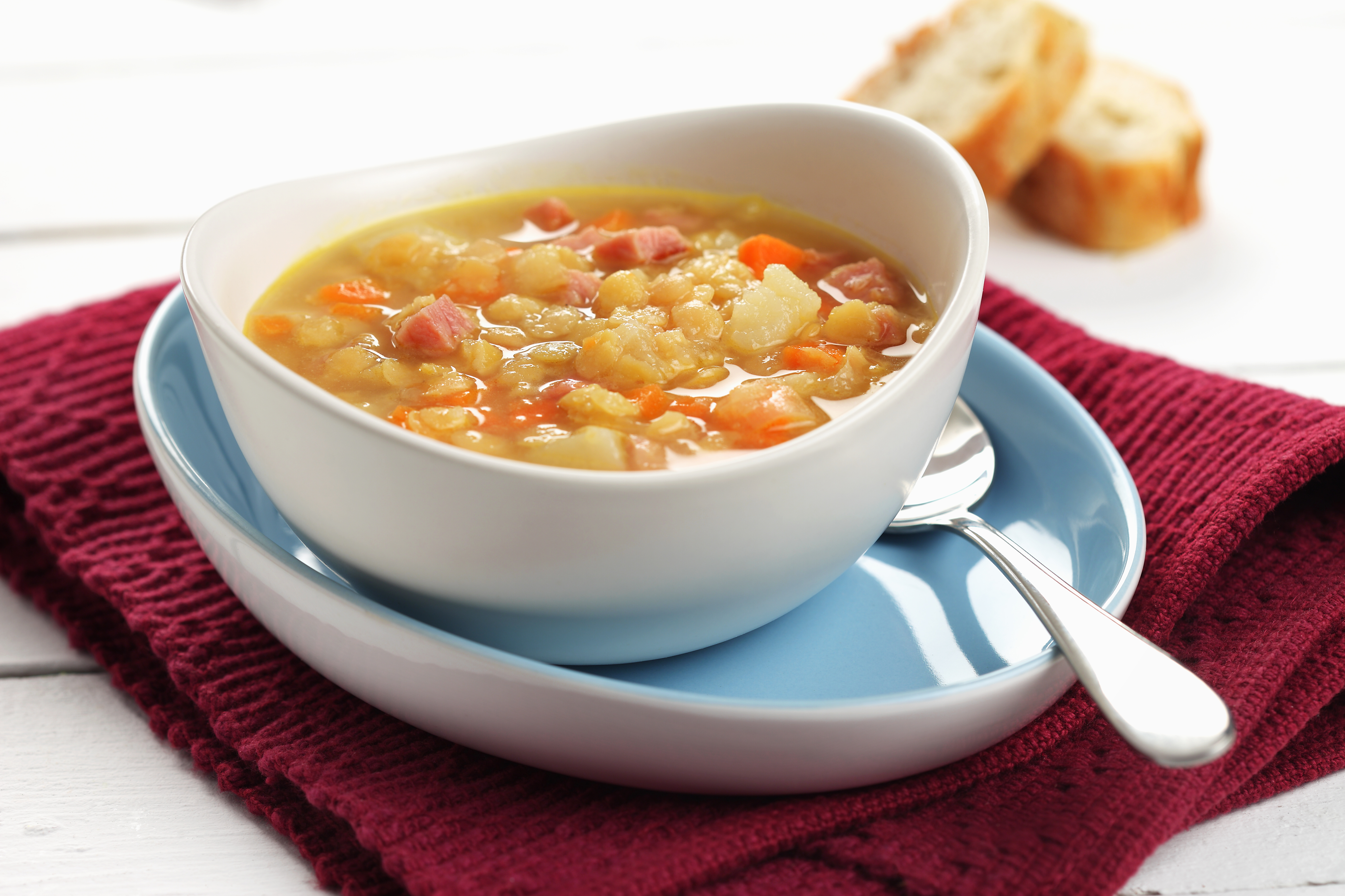 Bowl of soup with diced onion, carrots, potato and split peas