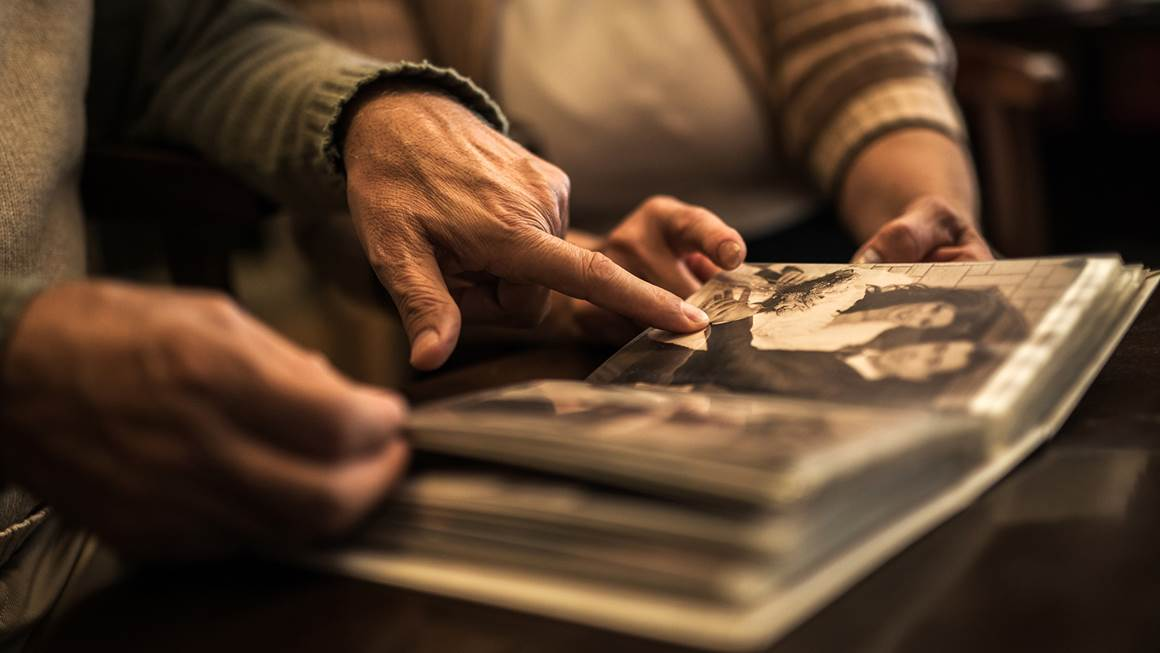 Closeup of elderly couple looking at photo album
