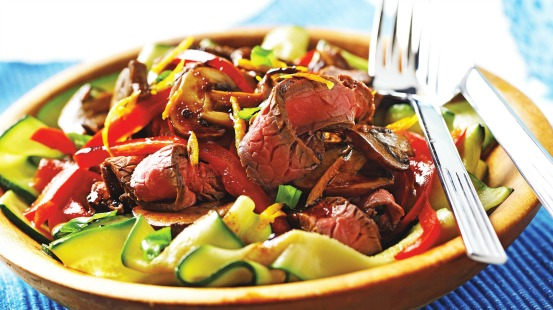 Slices of beef, zucchini ribbons and red peppers in a bowl