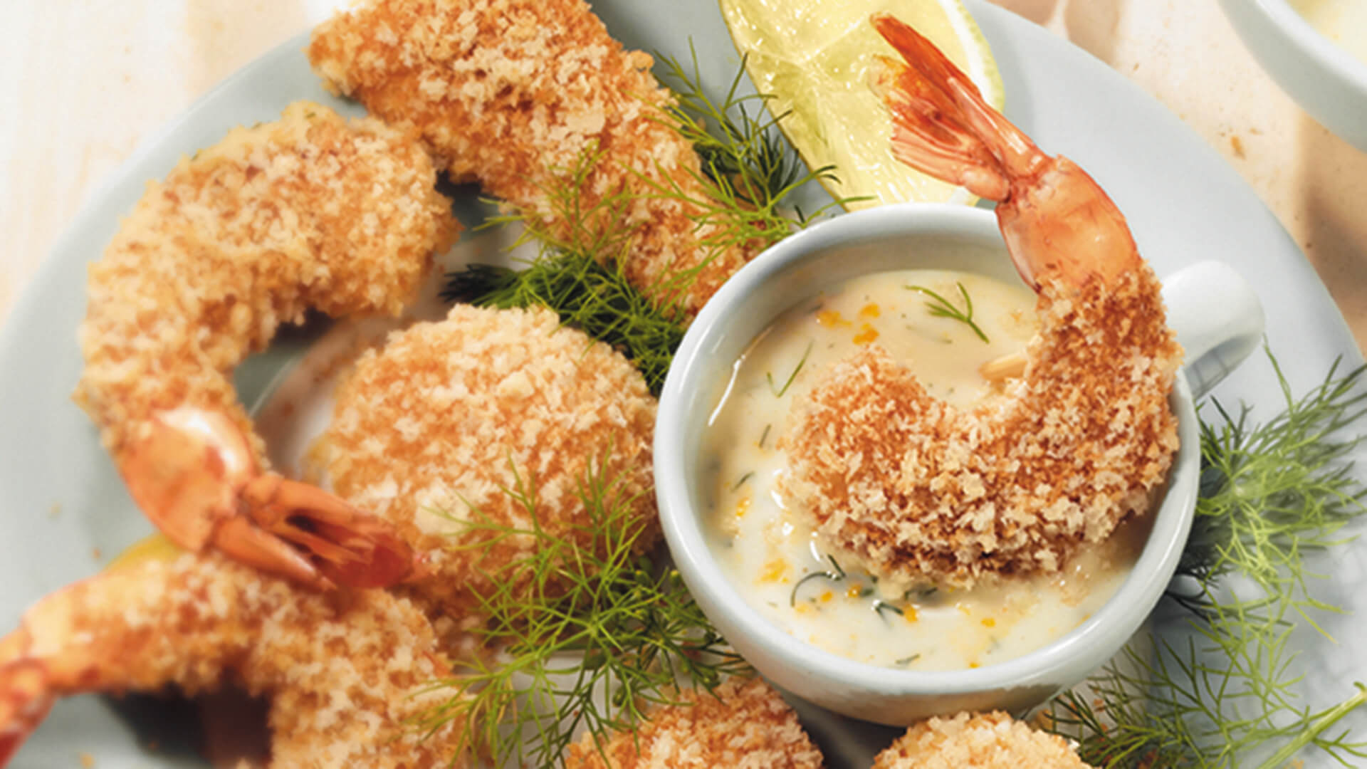 Breaded shrimp with dipping sauce and dill
