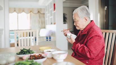 Elderly man eating from bowl with chopsticks