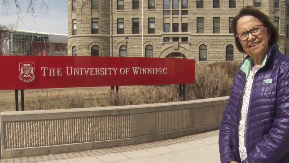 Esther Sanderson wears a purple jacket and smiles beside a University of Winnipeg sign.