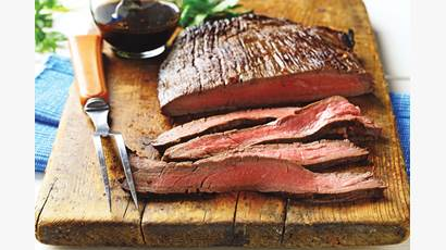 Sliced flank steak on wooden cutting board