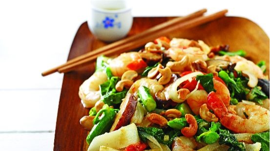 Shimp, bok choy, red peppers, cashews on wooden board with chopsticks