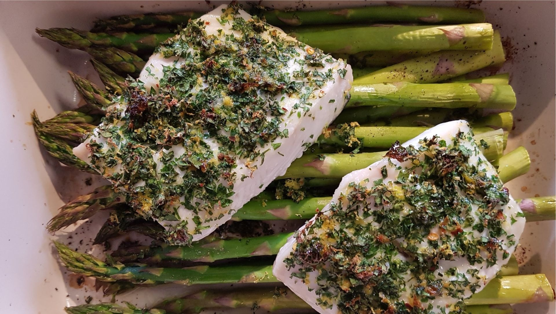 Halibut and asparagus spears in baking pan