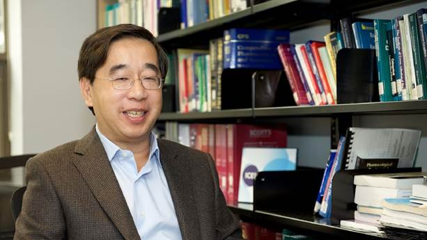 Dr. Jack Tu in front of a bookshelf