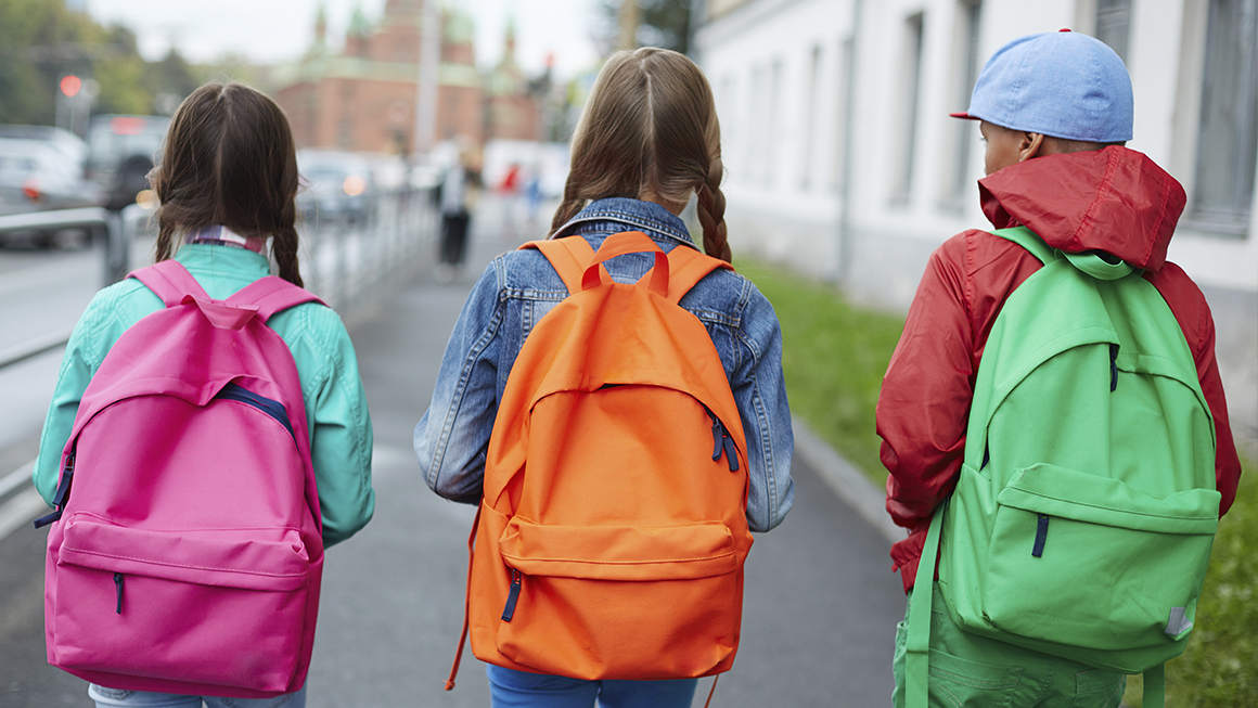 Three children walking to school with backpacks on.