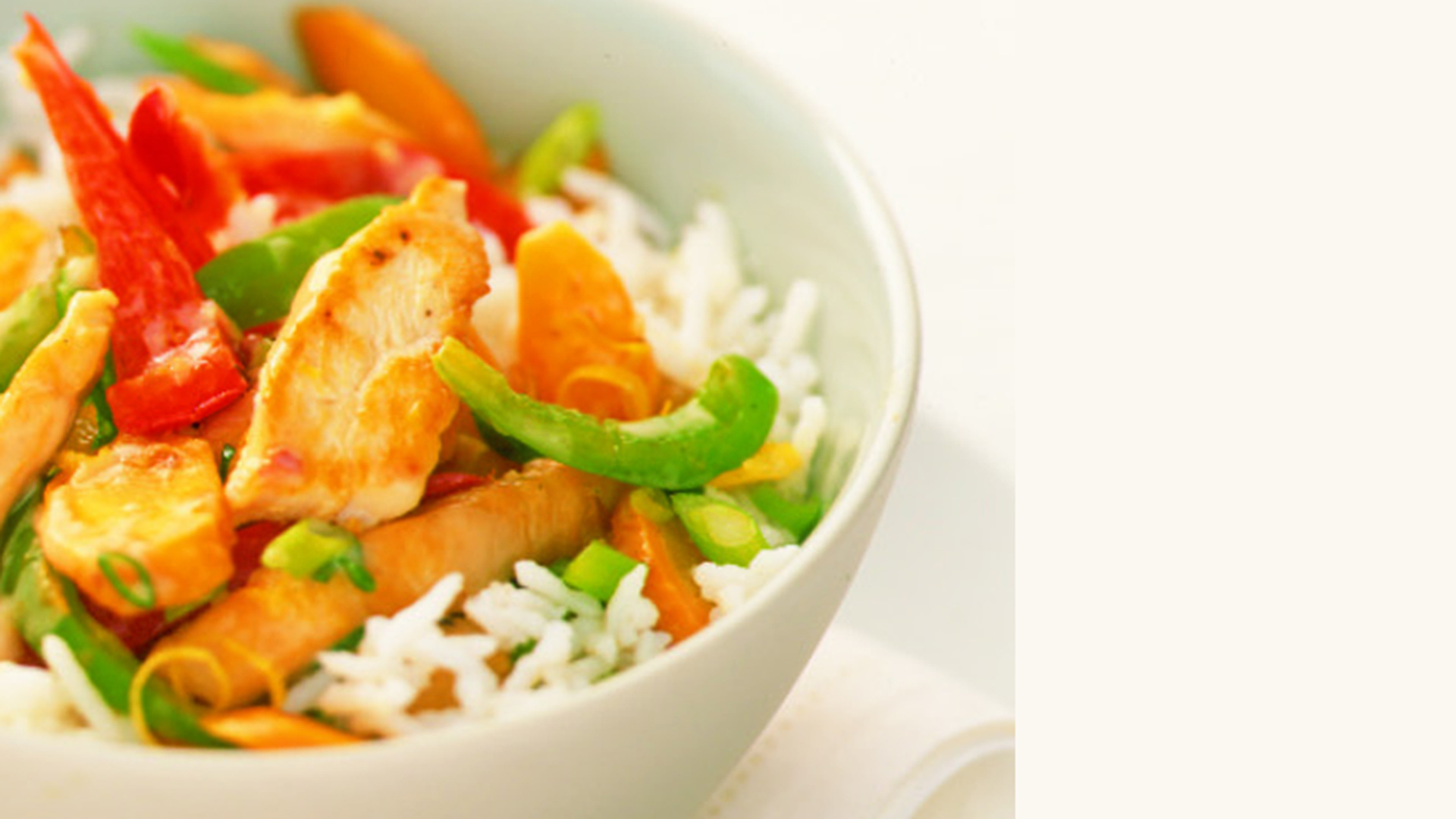 Bowl of rice with cooked chicken, red and green peppers