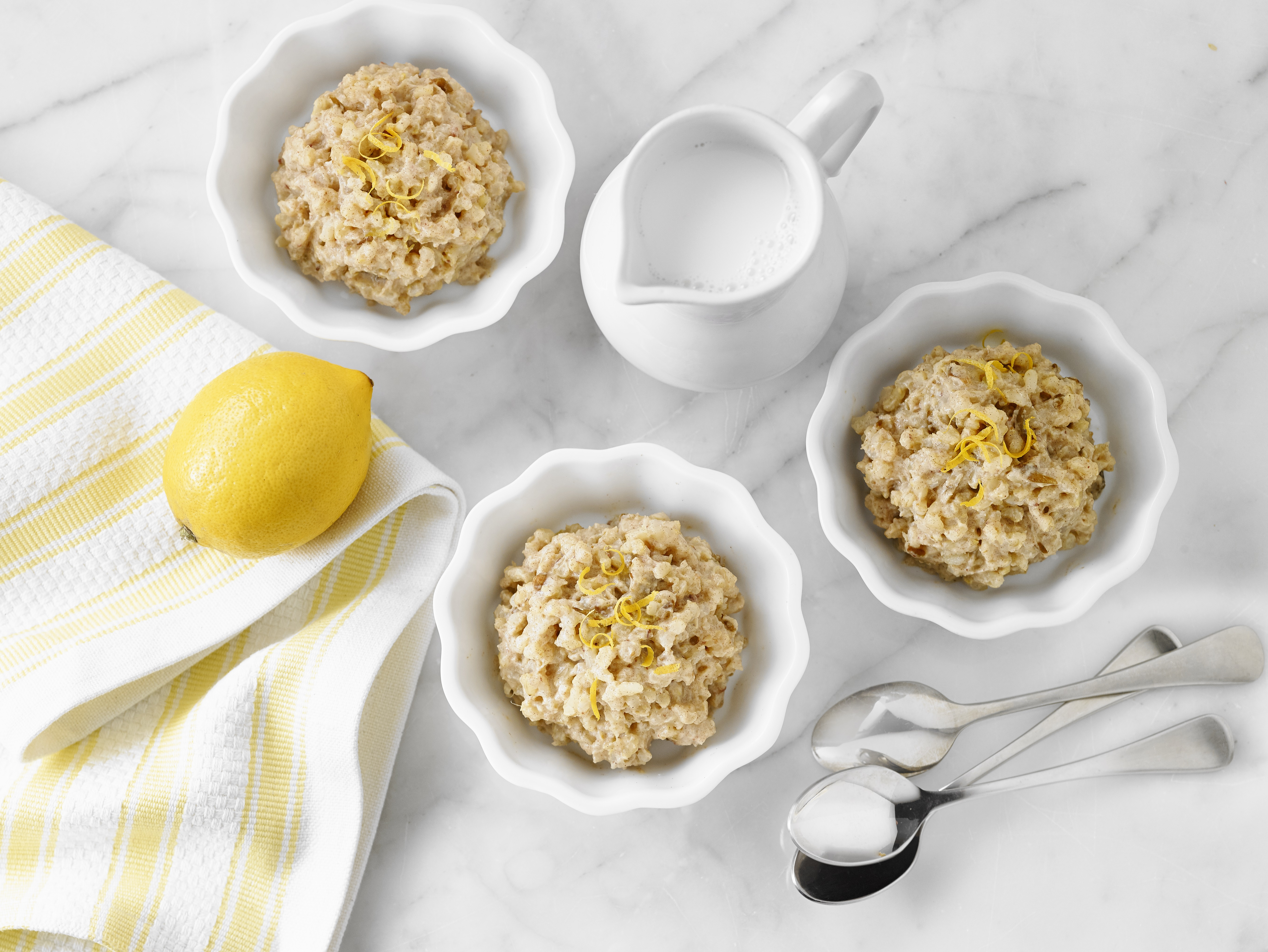 three bowls of lemon date rice pudding on white table cloth