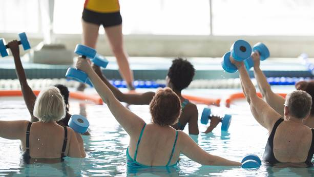 A group of senior women exercise in a pool.
