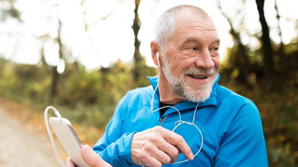 Man listening to music player while exercising outdoors