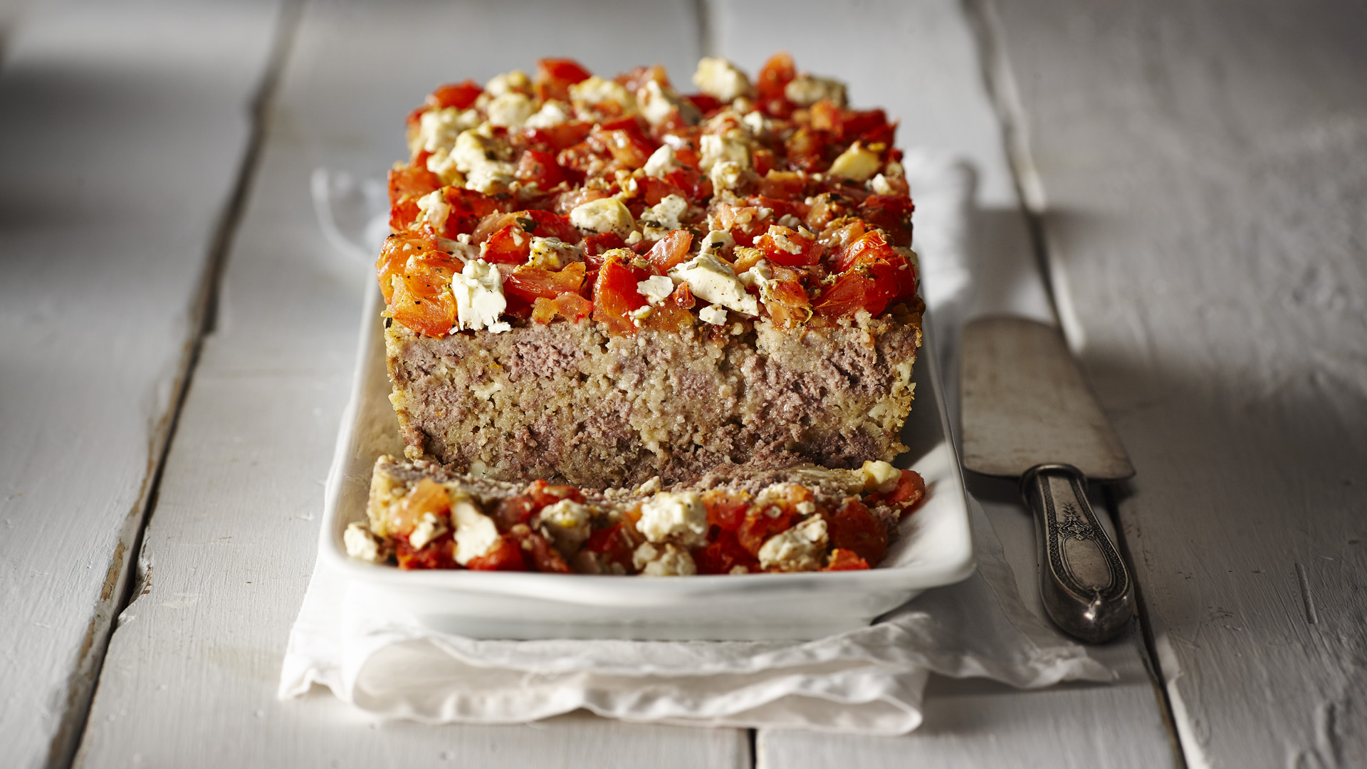 Meatloaf with tomatoes feta topping on white plate