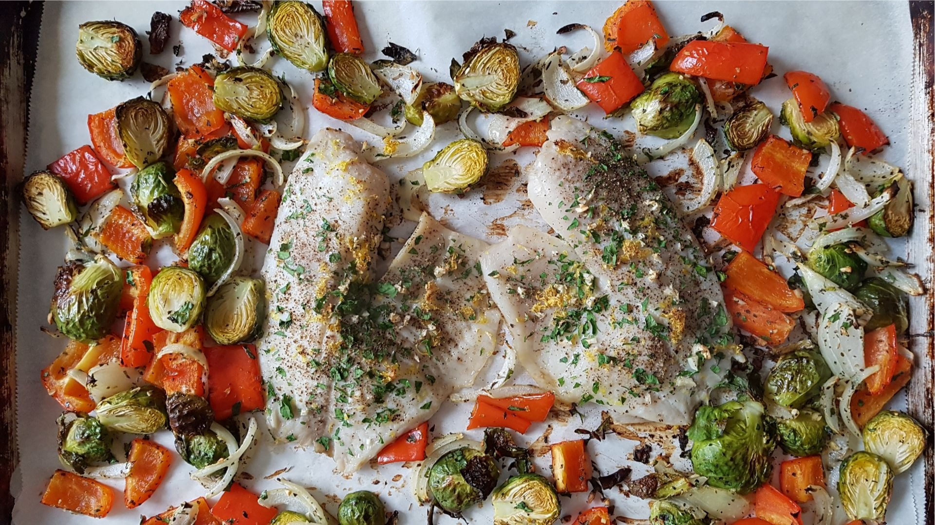tilapia fillets, brussel sprouts, red peppers on parchment paper